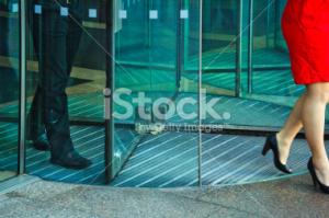stock-photo-30640540-busnessman-and-businesswoman-walking-through-revolving-door
